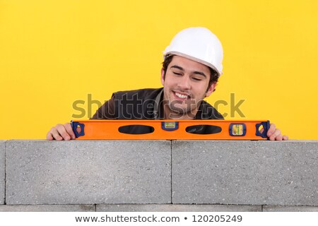 Up-beat mason using spirit-level on wall Stock photo © photography33