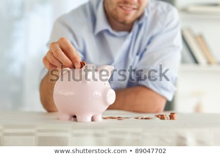 Small change being put into piggy bank Stock photo © wavebreak_media