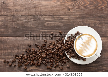 cup of coffee and beans on wooden table stock photo © justinb