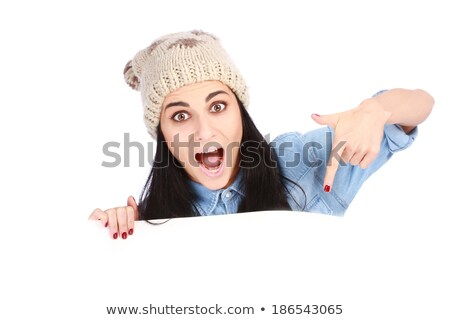 Young woman pointing her finger at a blank poster against a white background stock photo © wavebreak_media