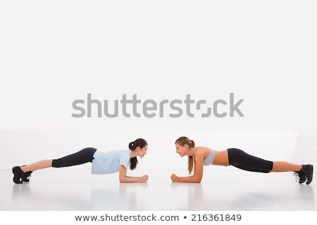 Smiling young woman practicing push-up exercises Stock photo © stryjek