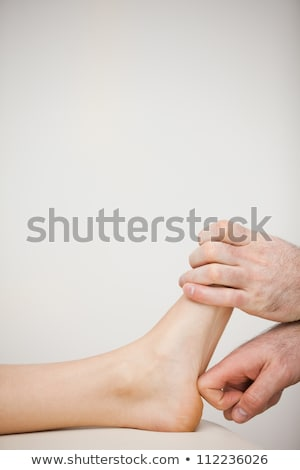 Stok fotoğraf: Physiotherapist Using His Forefinger To Massage A Foot In A Room