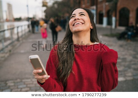 Smiling woman holding out her mobile phone Stock photo © dash