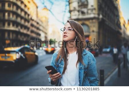 cheerful blond girl listening to music on her smartphone stock photo © stryjek