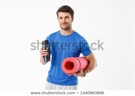 muscular sportsman practicing yoga on a mat over white background stock photo © deandrobot