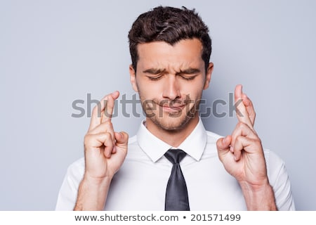 business man fingers crossed eyes closed Stock photo © godfer