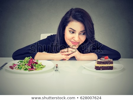 Stock photo: woman deciding whether to eat healthy food or sweet cookies she craving