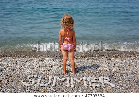Little girl stands on beach near water. From stones word is combined 'summer'. stock photo © Paha_L