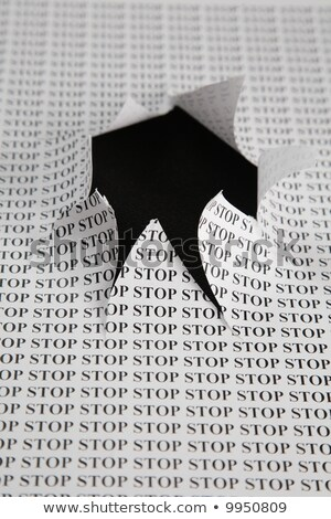 Stock photo: the sheet of paper with printing word stop and the cut hole against the black background 2