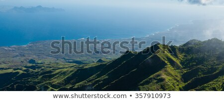 Steep green valley viewpoint leading to blue ocean coast of cape verde island Stock photo © attiarndt
