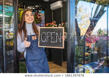 smiling young woman holding watering can with bouquet of flowers stock photo © deandrobot