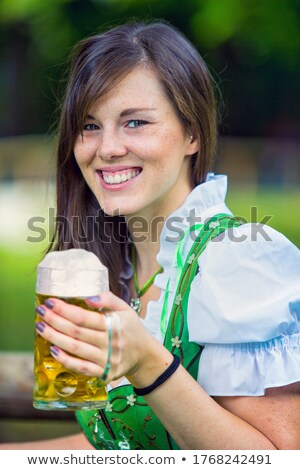 Young woman holding a beer mug in the beer garden Stock photo © kb-photodesign