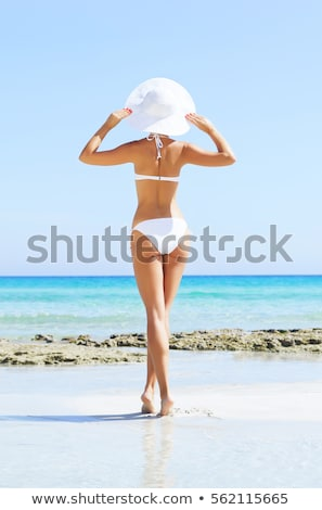 lány · fehér · bikini · sétál · tengerpart · szalmakalap - stock fotó © dolgachov