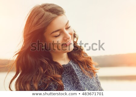 Portrait of a lovely young woman sitting with closed eyes Stock photo © deandrobot
