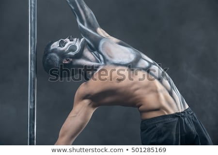 Pole dancer with body-art in dark studio Stock photo © bezikus