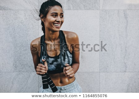 Smiling fitness woman standing and holding skipping rope Stock photo © deandrobot