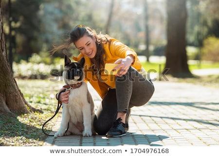 Adolescente menina telefone móvel cãozinho animal de estimação grama Foto stock © lunamarina