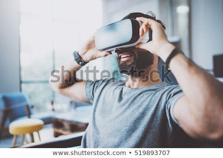 Young bearded man wearing virtual reality device Stock photo © deandrobot