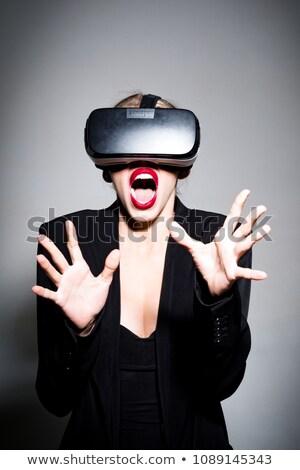 Beautiful scared lady wearing virtual reality device Stock photo © deandrobot