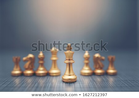 close up of white chess pieces with golden queen stock photo © ankarb