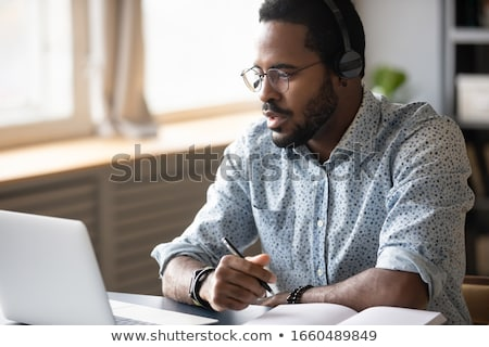 Concentrated young bearded businessman wearing glasses Stock photo © deandrobot