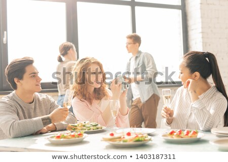 Woman at party getting sandwich from food table smiling Stock photo © monkey_business