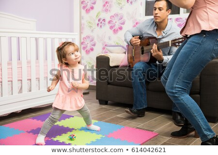 Man playing acoustic guitar for daughter in living room Stock photo © boggy