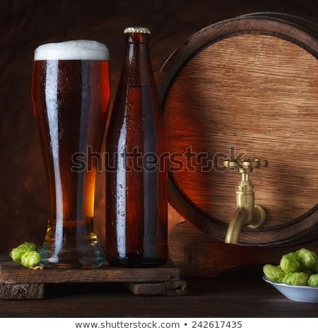 Cold glass of craft beer on old wooden barrel stock photo © DenisMArt