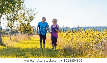Dois saudável senior pessoas corrida estrada rural Foto stock © Kzenon