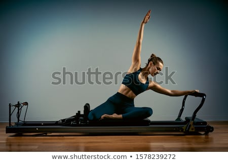 gym woman pilates stretching sport in reformer bed stock photo © lunamarina