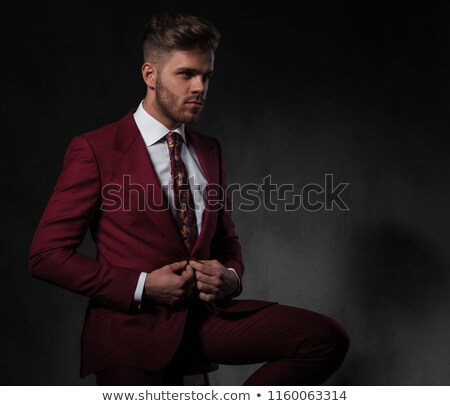 seated man buttons his red suit while looking to side stock photo © feedough