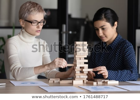 Team of young business people build a wooden construction in the Stock photo © boggy