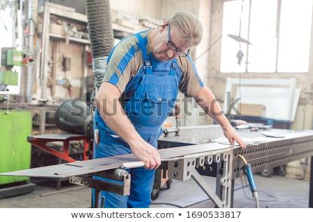 Metalworker man in his workshop working on project Stock photo © Kzenon