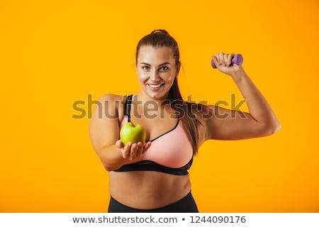 Portrait of european chubby woman in sportive bra holding apple, Stock photo © deandrobot
