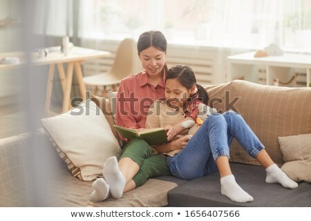 cheerful mother reading a novel for her children stock photo © konradbak