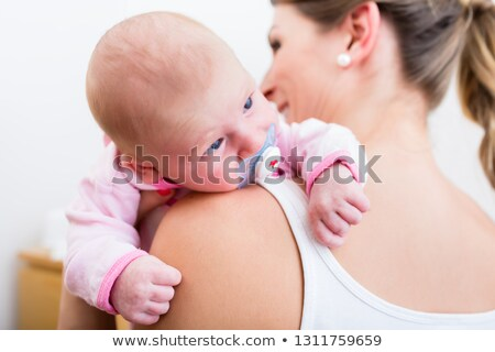 mother carrying her baby sucking pacifier stock photo © kzenon
