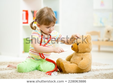 A doctor girl playing and cure bear at the pediatric Stock photo © Lopolo