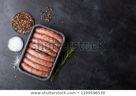 Raw beef and pork sausage in plastic tray with vintage fork on black background.Salt and pepper with Stock photo © DenisMArt