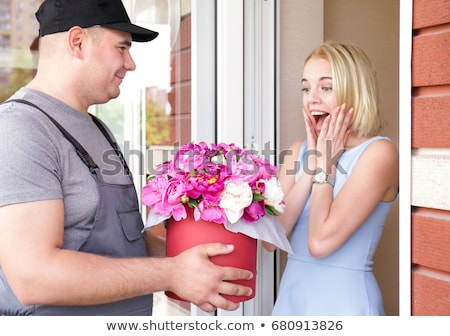 Delivery man holding flower bouquet gift Stock photo © Kzenon