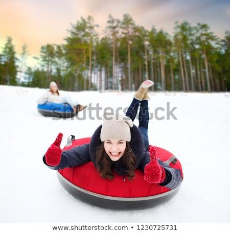 happy teenage girl sliding down hill on snow tube Stock photo © dolgachov