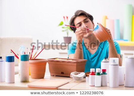 Young man decorating pottery in class Stock photo © Elnur