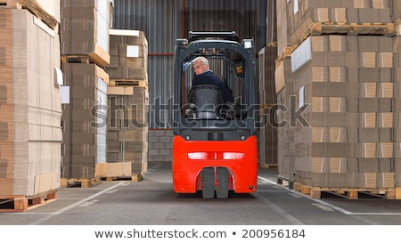 Worker in logistics distribution center with his forklift Stock photo © Kzenon