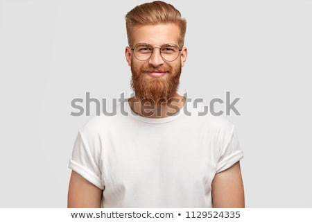 Portrait of satisfied Caucasian male with stubble, has gentle smile, wears stylish cap and shirt, lo Stock photo © vkstudio