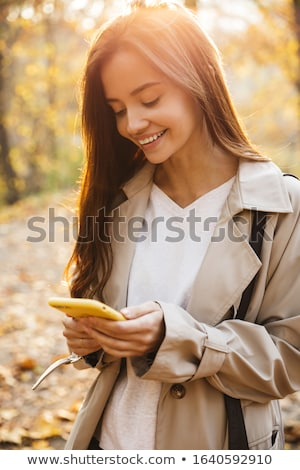 Image of young woman using smartphone while walking in autumn pa Stock photo © deandrobot