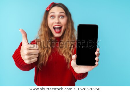 Image of delighted nice woman showing cellphone and thumb up Stock photo © deandrobot