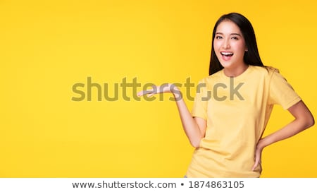Good looking woman showing a copy space with her finger while standing against a white background stock photo © wavebreak_media