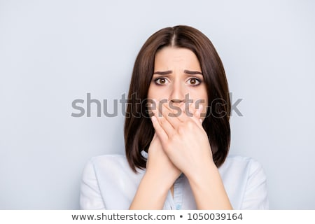 Businesswoman covering her mouth with palms Stock photo © deandrobot