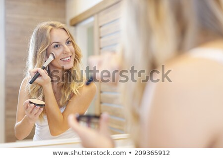 smiling woman applying brushes and doing makeup in bathroom stock photo © deandrobot