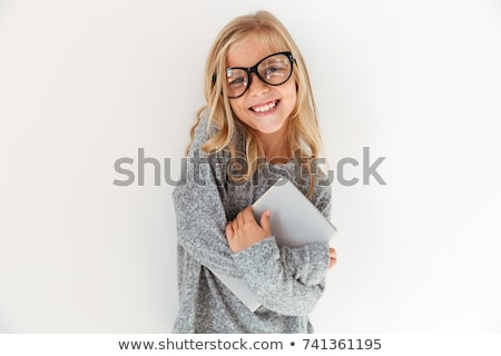 Cheerful little girl in gray pajamas holding book, looking at ca Stock photo © deandrobot