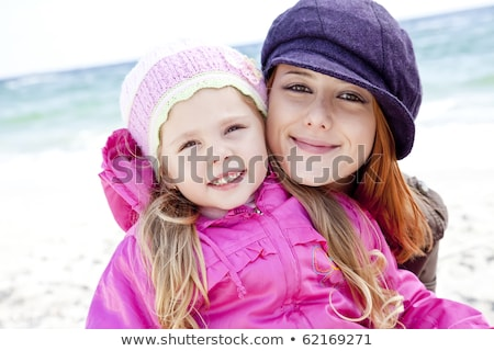 two sisters 4 and 21 years old at the beach in sunny autumn day stock photo © massonforstock